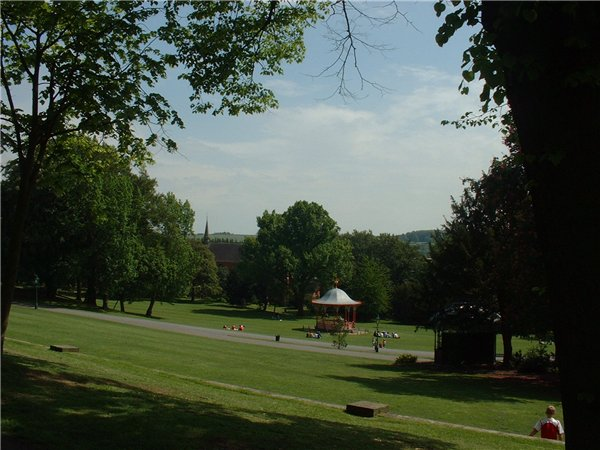 View of red and white cast-iron bandstand and surrounding grassed areas.