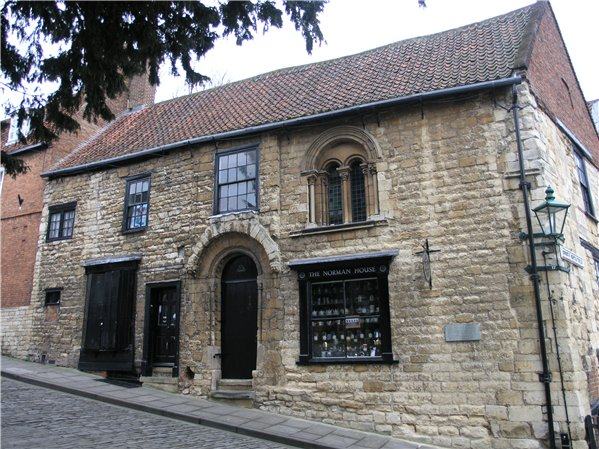 12th century stone-built Norman House, a landmark building in the far north of the Character Area, and terminating building to views up the slope along Steep Hill. Note the integrated shop window on the right hand side of the building.