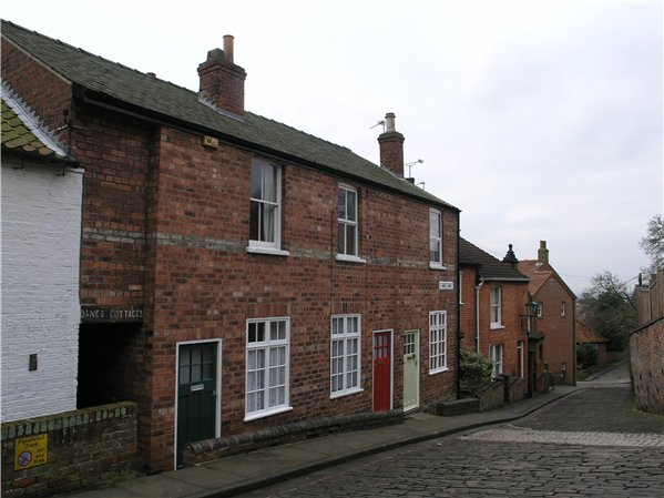 Two storey terraced cottages with simple decoration along Well Lane