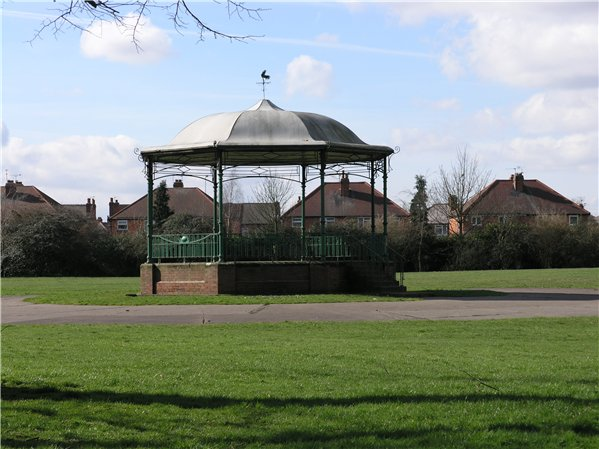 Bandstand with a grassed area around it base and then a pathway circling around it with it joining onto the bandstand for access where the steps are located. Around this footpath is a bigger grassed expanse with trees shading some of the view to nearby pr