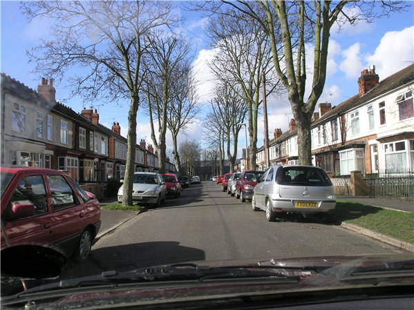 Terraced houses on Church Drive, which each have bay windows on the ground floor. The street is lined by trees either side.