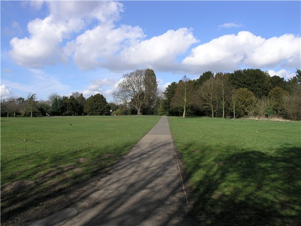 Large open grassed areas with wooded edges and footpath across the middle.