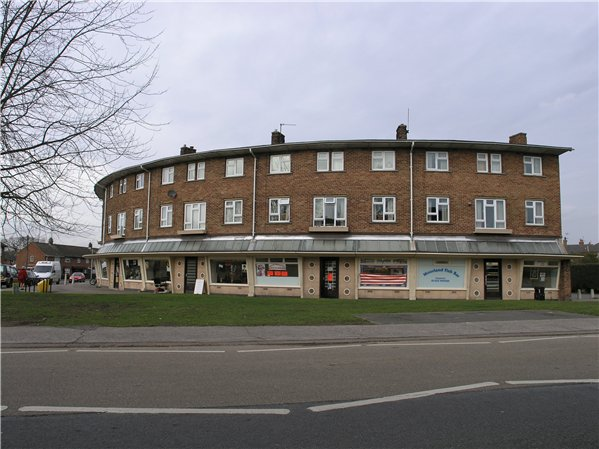 The row of shops is a curved three-storey landmark building with a shallow pitched gabled roof with deep eaves and brown pantiles. The row has a curving projection with a glass roof at first-floor level which provides cover along the shop fronts