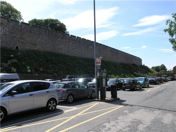 Castle walls with car park in front of it