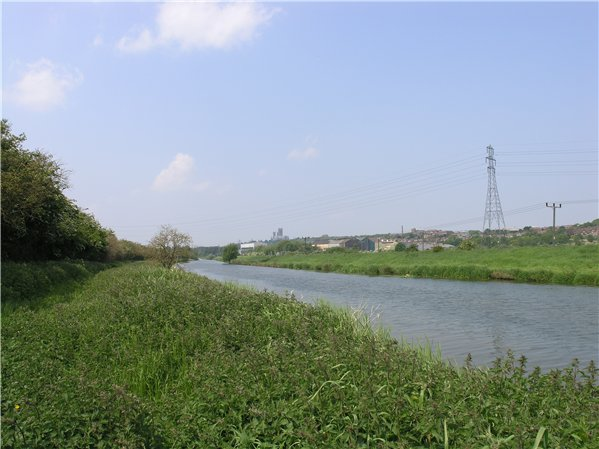 Looking west along the River Witham. The Cathedral is visible in the background with large industrial units in front of it and housing developments to the east.