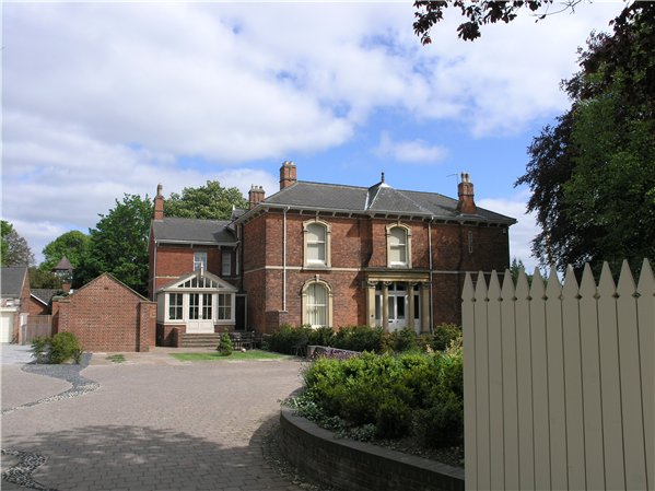 Large detached property from the Late Victorian/Edwardian period with a classical-style doorway and later additions such as a conservatory