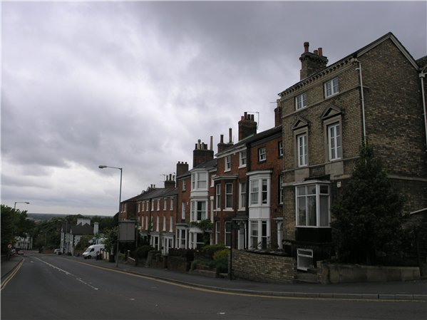 View of terraced properties along Lindum Hill. They are consistently two bays in width and three storeys high but there is a staggered roof line due to the gradient of the hillside.