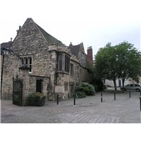 Stone buildings and public realm opposite the cathedral on Minster Yard. The public realm is paved in natural stone materials denoting the footways and carriageway.