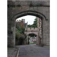 Looking towards the Bishop's Palace through two arches that are formed between walls.